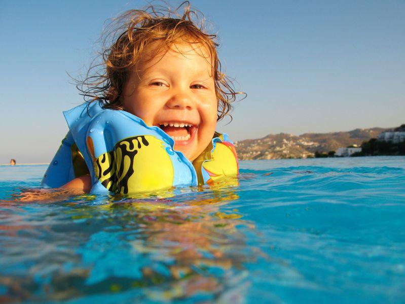 la bambina divertente nuota in uno stagno in bracciali gonfiabili gialli