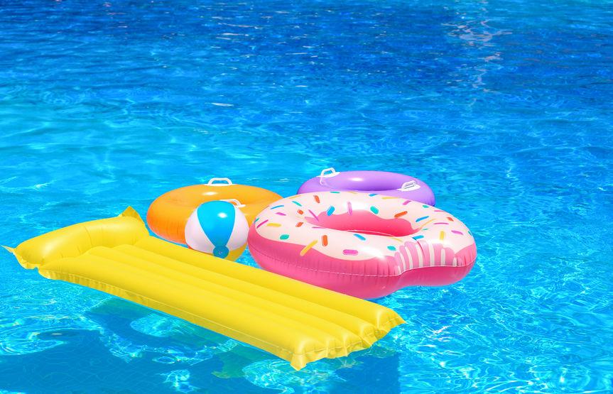 Anelli gonfiabili, materasso e palla nella piscina blu