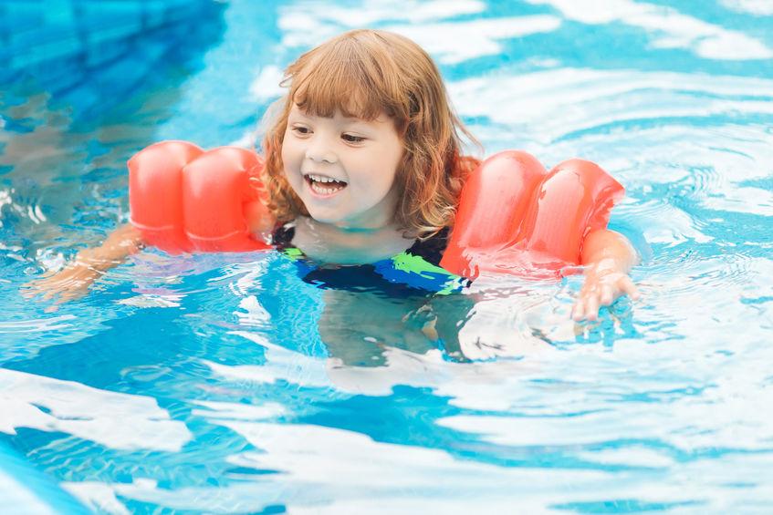 Adorabile bambina con maniche gonfiabili galleggia in piscina.