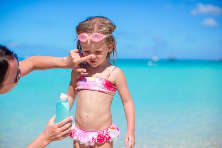 Madre che mette la crema solare alla figlia