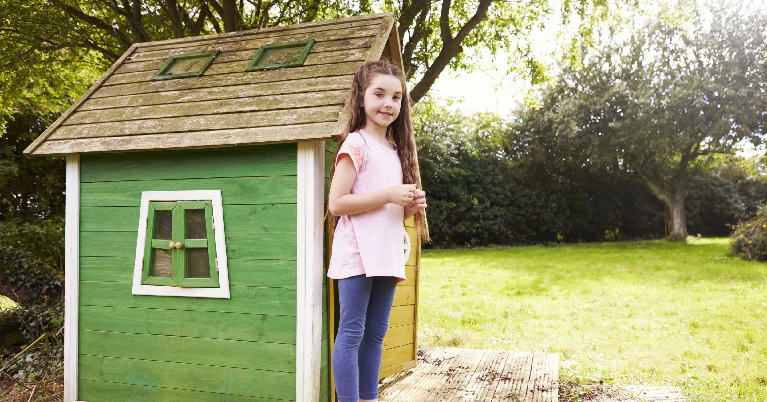 Portrait Of Girl Standing In Garden Next To Playhouse