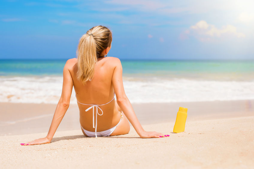 Woman with UV protection cream bottle on the beach