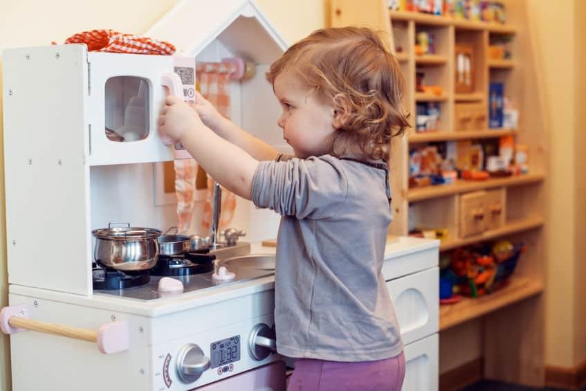 Bambina aprendo sportello di una cucina giocattolo