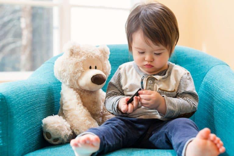 Un bimbo su una poltrona per bambini con un orsetto