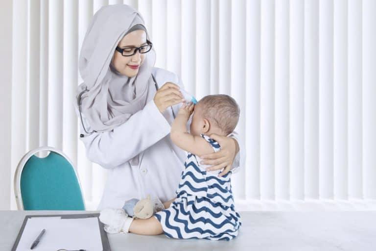 Pediatra che misura la febbre a una bambina