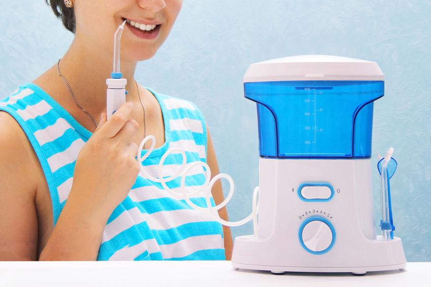 bella ragazza si lava i denti con un irrigatore orale.