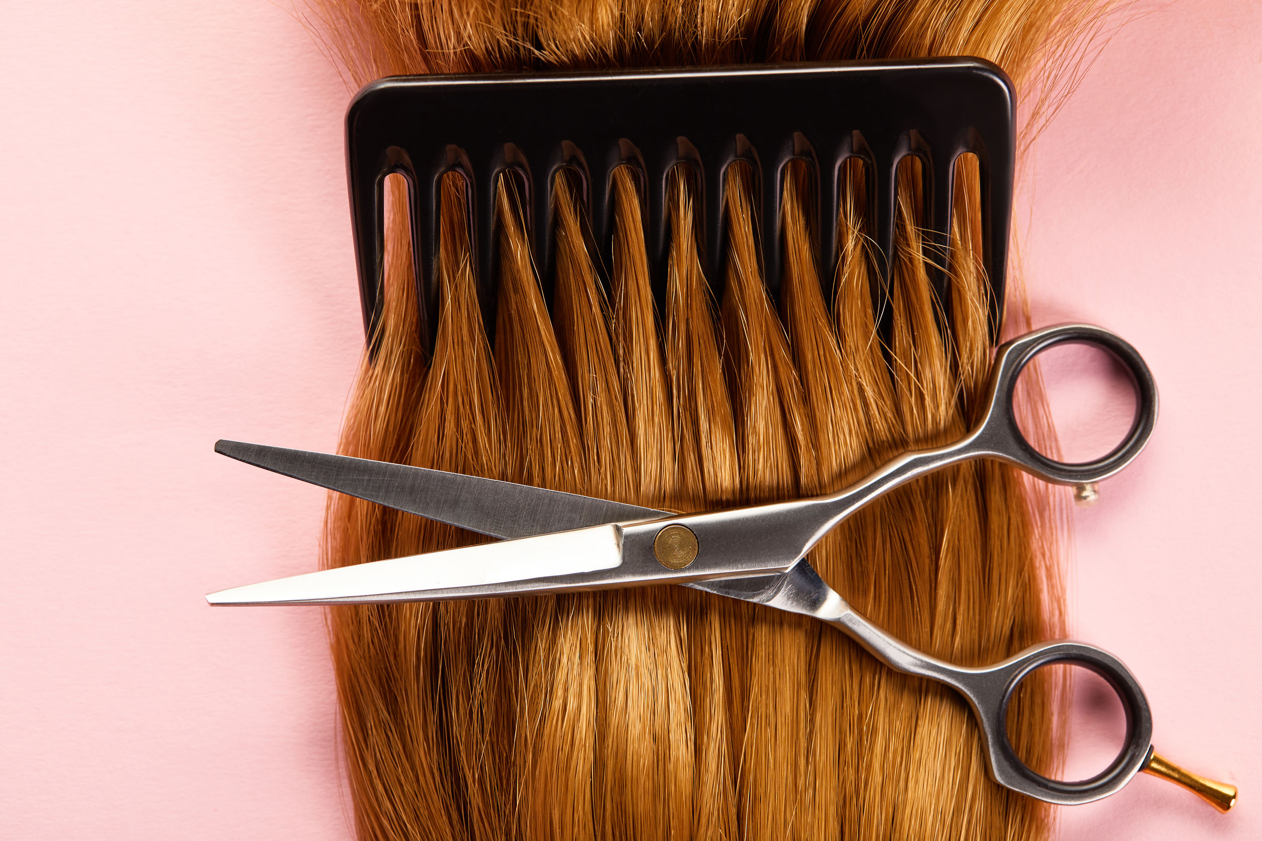 Top view of scissors, comb and brown hair on pink background