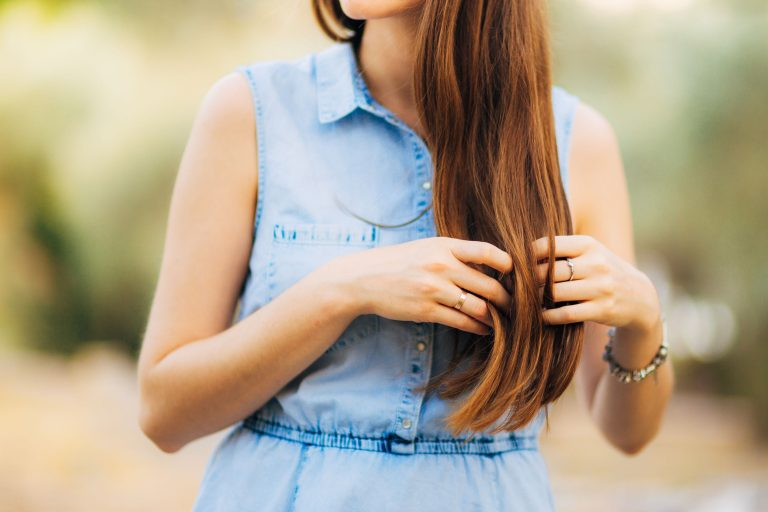 Donna in vestito blu che tocca i suoi capelli