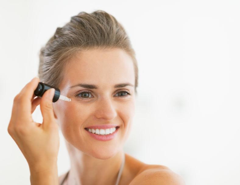 Ritratto di giovane donna felice che applica siero cosmetico