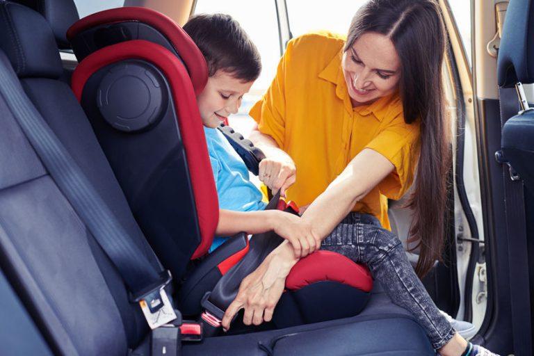 Mamma che sistema il seggiolino auto del figlio