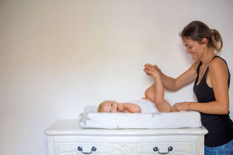 Donna che cambia il figlio su un coprifasciatoio