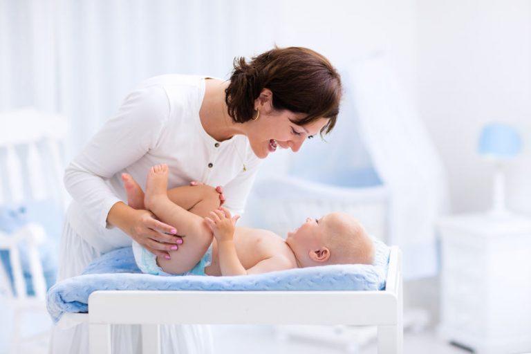 Mamma che sorride al figlio sul fasciatoio