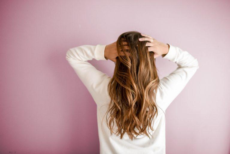 Immagine di donna da dietro toccando i capelli su sfondo viola