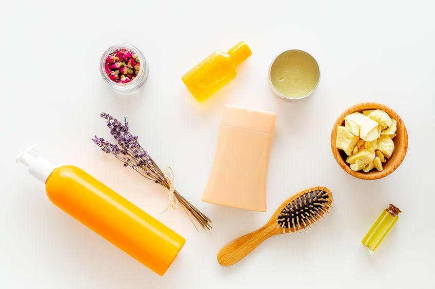 Cosmetici per la cura dei capelli con jojoba, argan o olio di cocco. Bottiglie e pezzi di olio sulla vista superiore del fondo bianco.