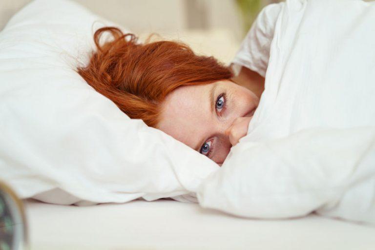 Donna sorridente sotto le lenzuola