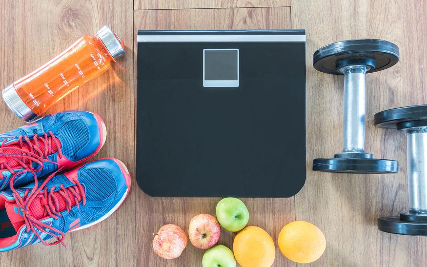 Frutta, attrezzi per allenarsi e bilancia pesapersone