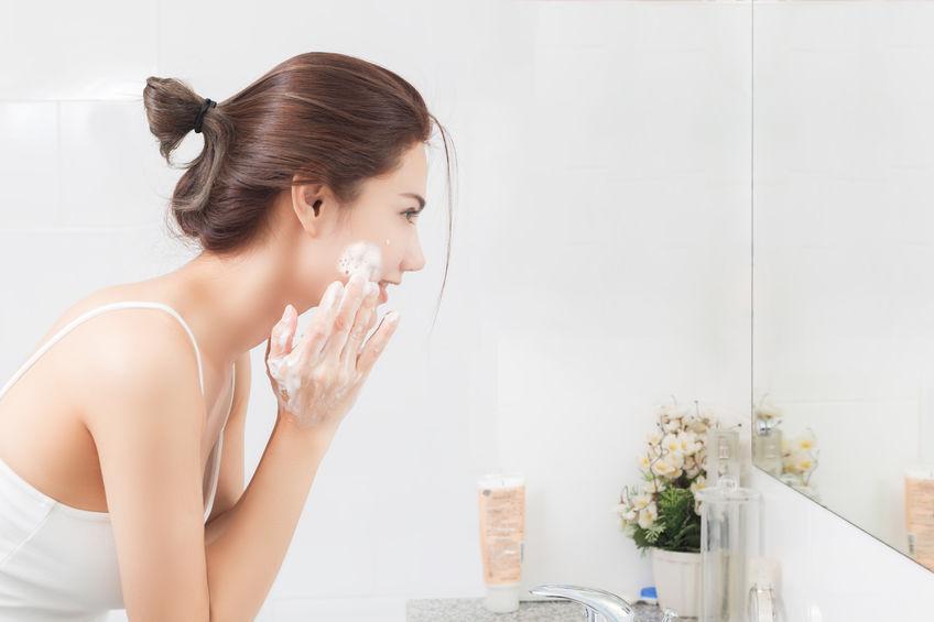 Donna davanti allo specchio che si insapona il viso