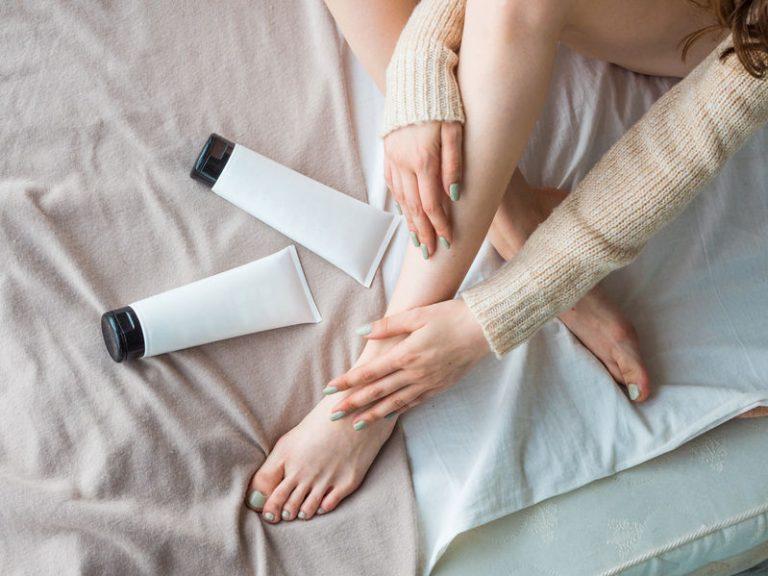 Gambe di donna con due barattoli di crema vicino