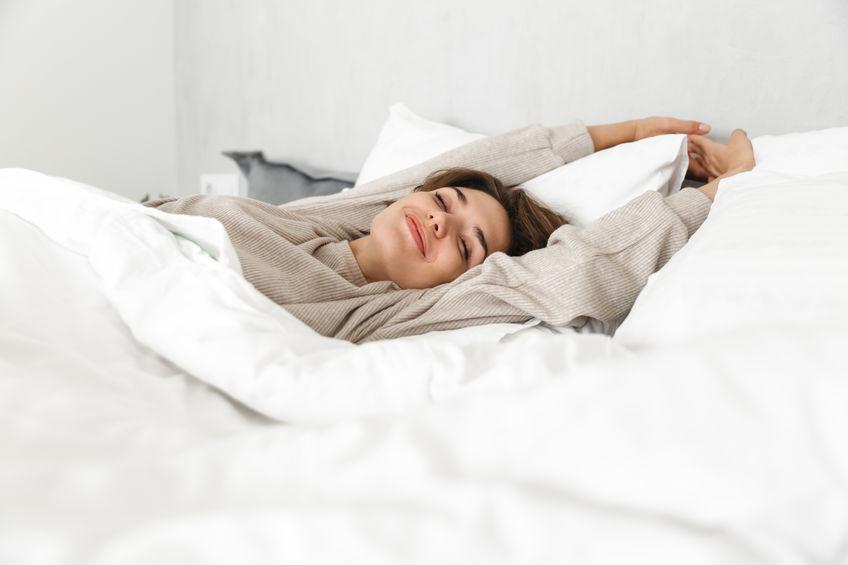 Donna che si sveglia nel letto soddisfatta