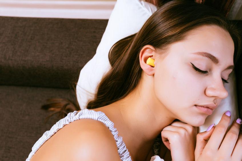 Giovane donna che dorme con i tappi