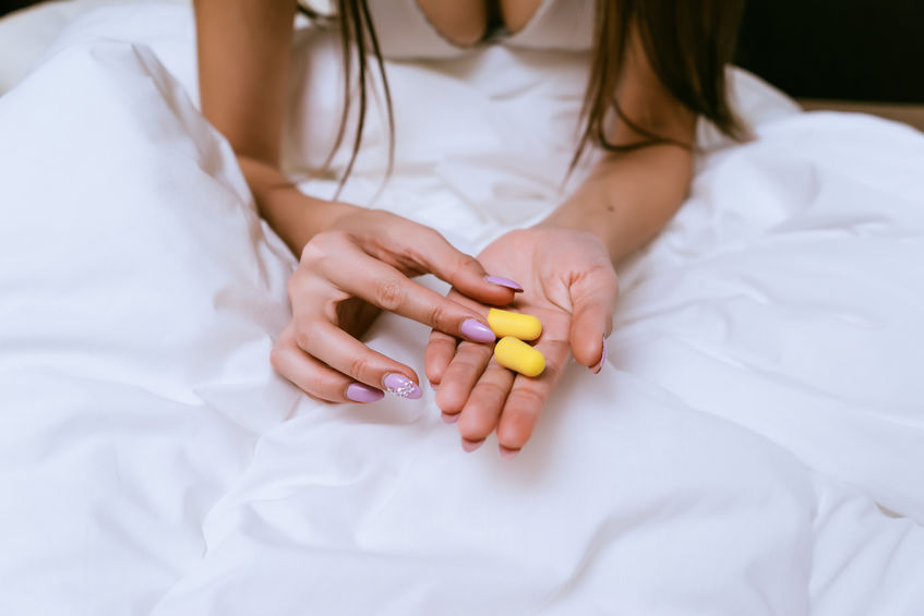 Donna con in mano due tappi per le orecchie gialli