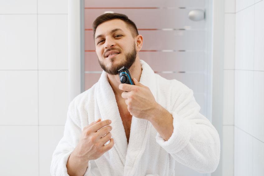 Uomo che si rade la barba davanti allo specchio