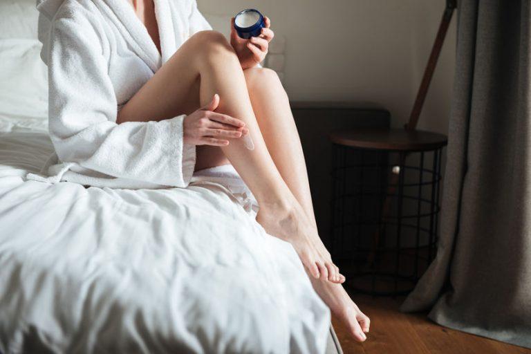 Donna che si passa una crema sulle gambe