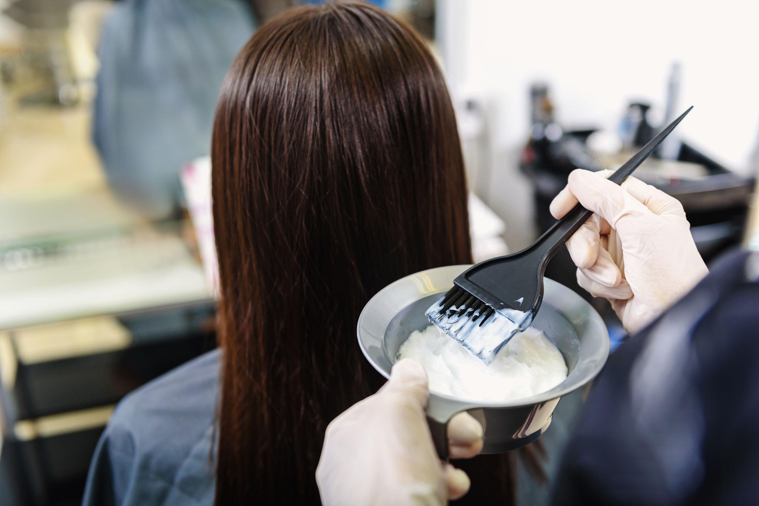 Estilista aplicando acondicionador en cabello de mujer