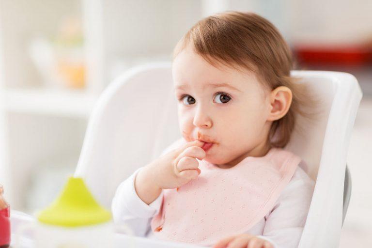 Una niña usando un babero para comer