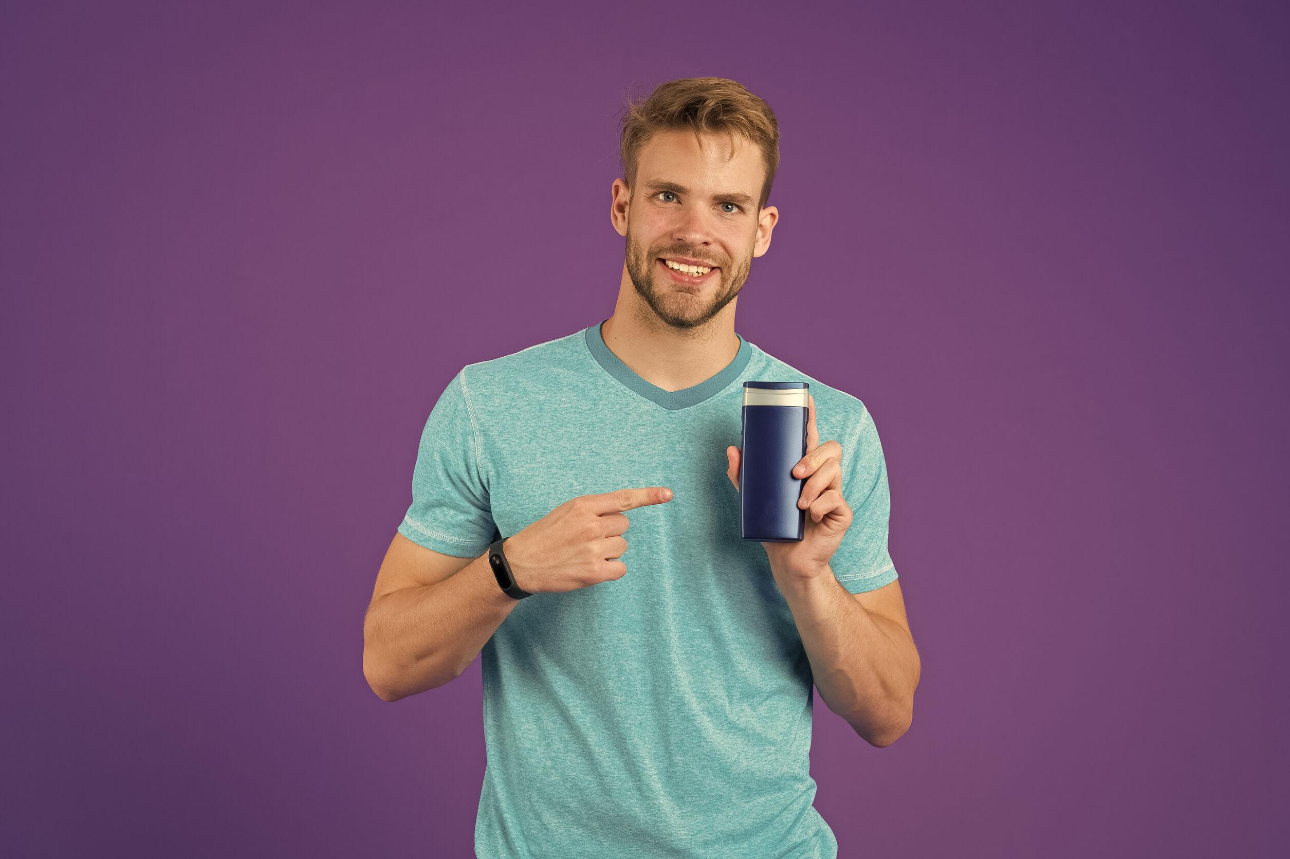 Hombre feliz señalar con el dedo al tubo de gel sobre fondo violeta