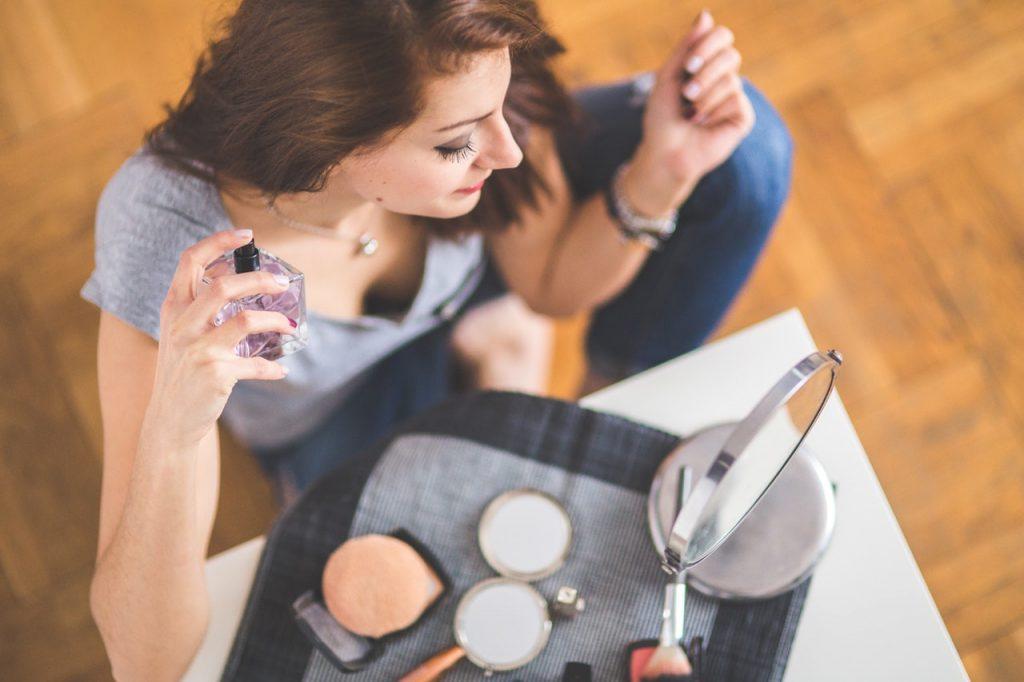 Foto de uma mulher aplicando perfume no pescoço em frente uma mesa com maquiagens e espelho.
