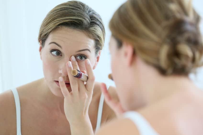 Foto de mulher aplicando corretivo na frente do espelho.