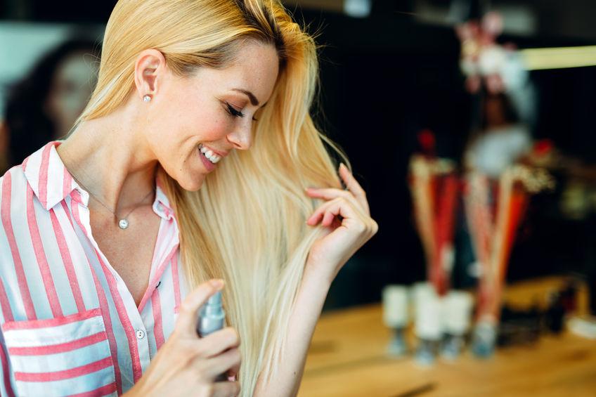 Imagem de uma mulher borrifando queratina nos fios.