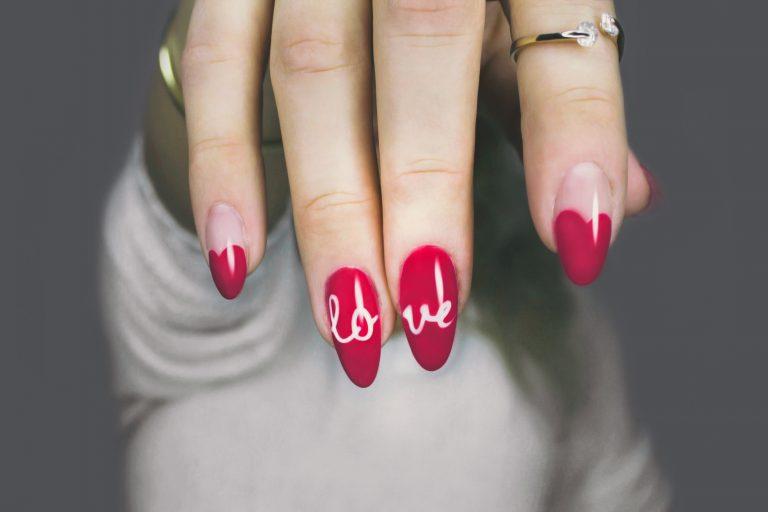 """Foto de uma mão com unhas de pontas ovais, e esmalte rosa e branco, em que os dois dedos do meio, juntos, formam a palavra """"love""""."""