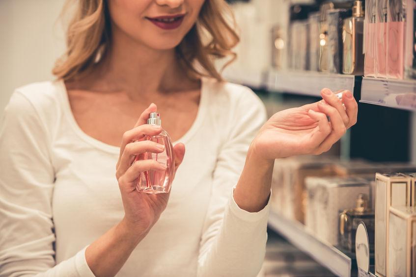 Imagem de mulher borrifando perfume no pulso.