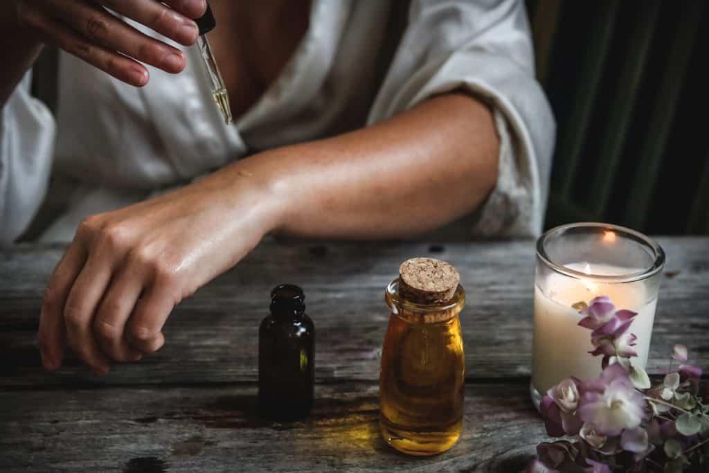 Imagem de uma mulher aplicando óleo de melaleuca na pele.