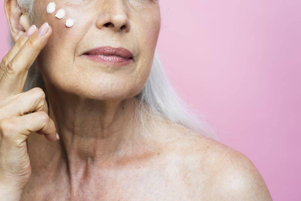 Senhora com cabelos longos grisalhos aplica creme facial em frente a um fundo rosa.