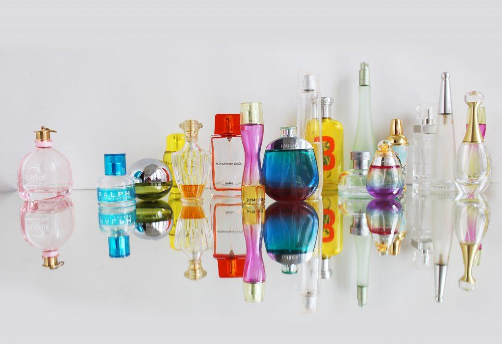 Muitos perfumes lado a lado em uma superfície espelhada.