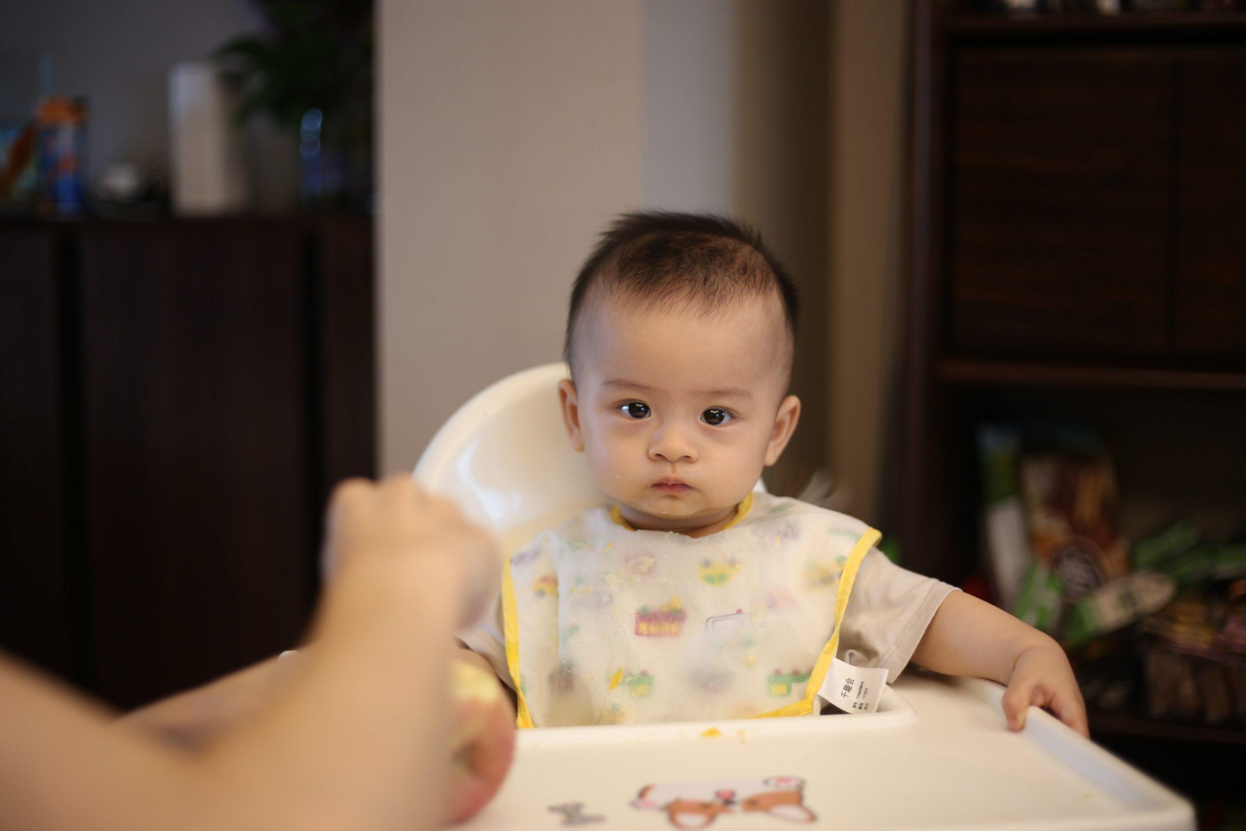 Bebê sentando em sua cadeirinha usando um babador