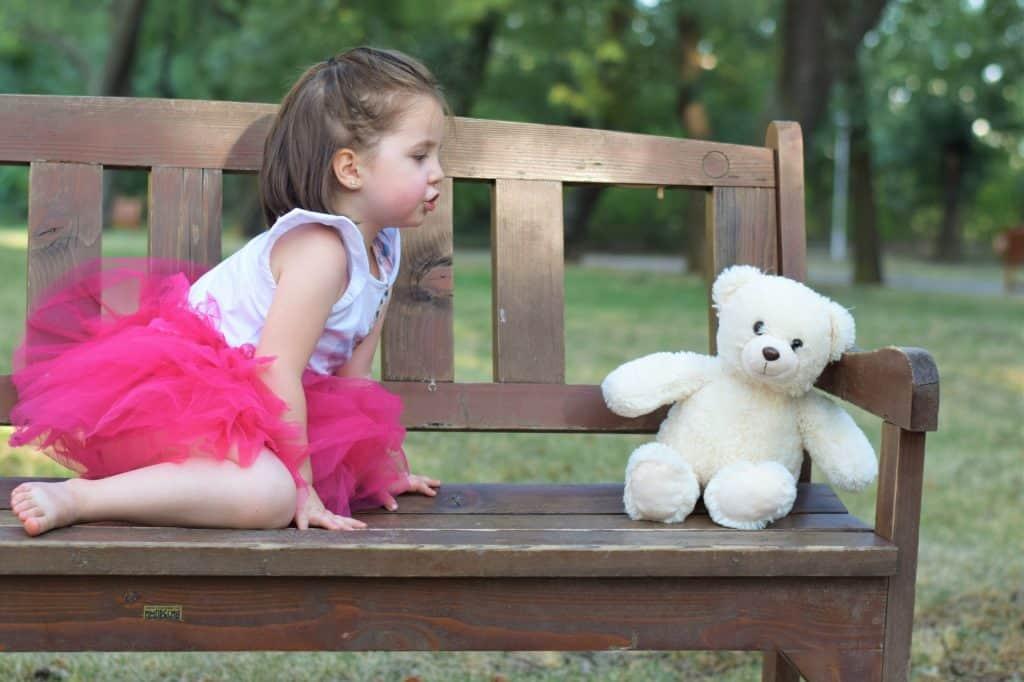 Na foto uma menina sentada em um banco de madeira ao lado de um ursinho de pelúcia.
