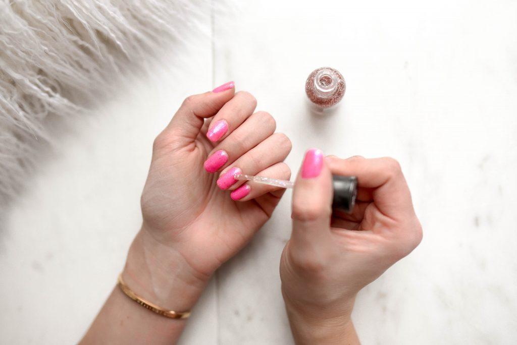 Imagem das mãos de uma mulher com unhas rosa e uma das mãos aplicando um esmalte com glitter sob o esmalte rosa da outra mão.