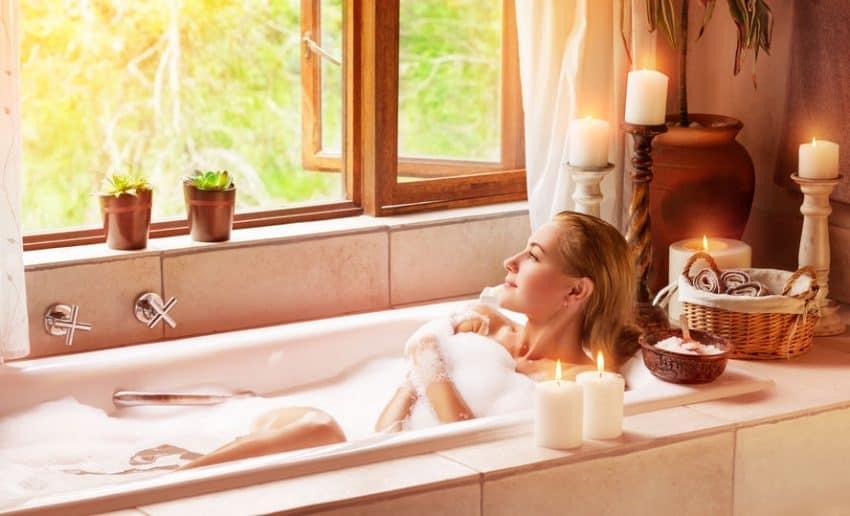 Mulher em banheira relaxando e olhando pela janela.