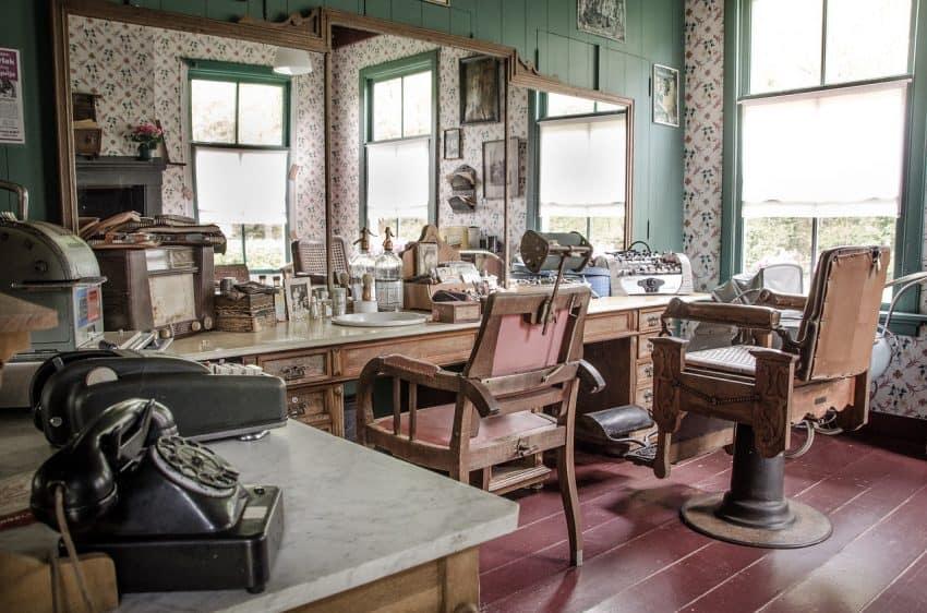Imagem mostra uma barbearia antiga com cadeiras e espelhos.