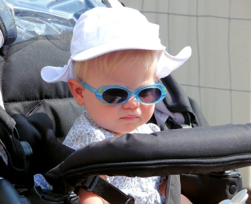 Imagem de uma criança sentada em um carrinho de bebê.