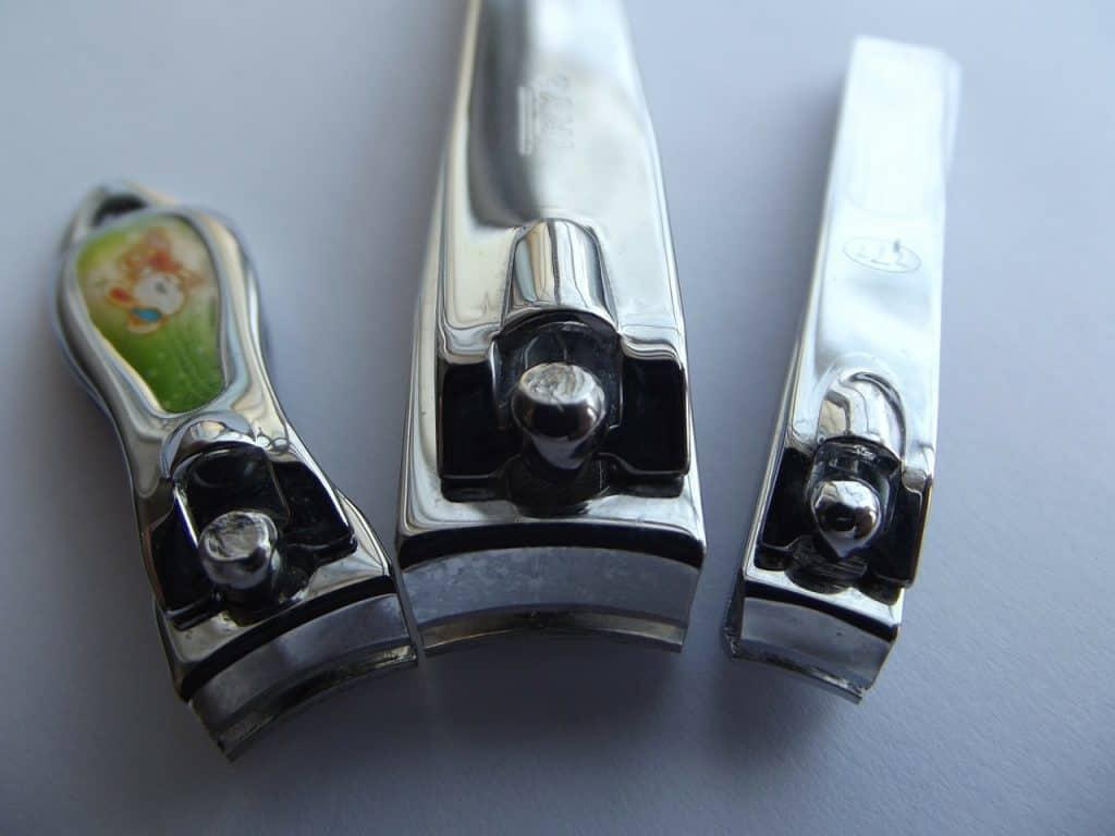 Imagem de três cortadores de unha enfileirados.