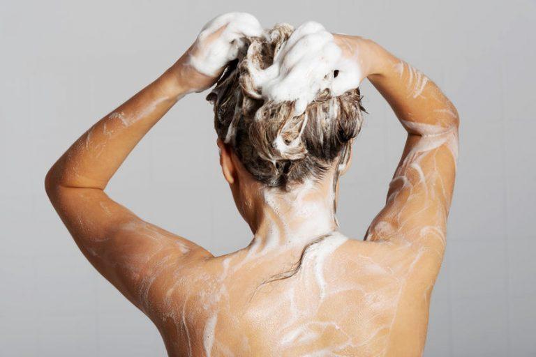 Foto de uma mulher tomando banho, com espuma pelos cabelos e corpo.