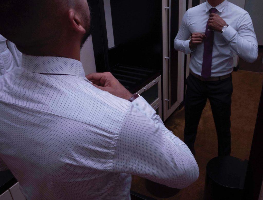 Imagem mostra um homem arrumando a gola de uma camisa social em frente ao espelho.
