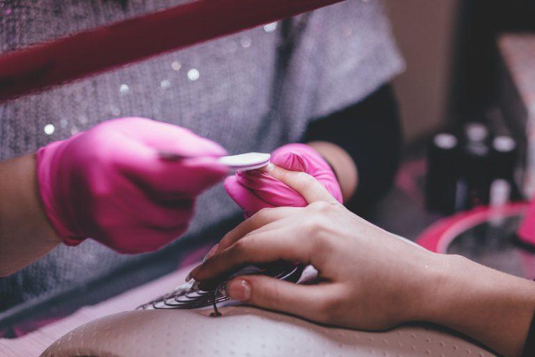 Foto de uma manicure de luvas rosas lixando a unha de uma pessoa.