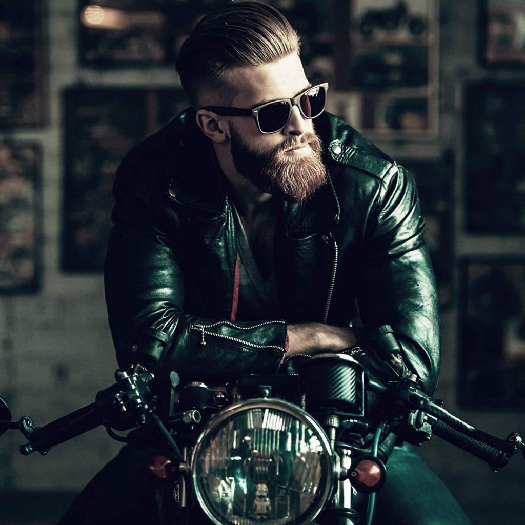 Um homem veste jaqueta de couro, óculos escuro, porta uma barba longa e cabelo modelado com gel está sentado em uma motocicleta.
