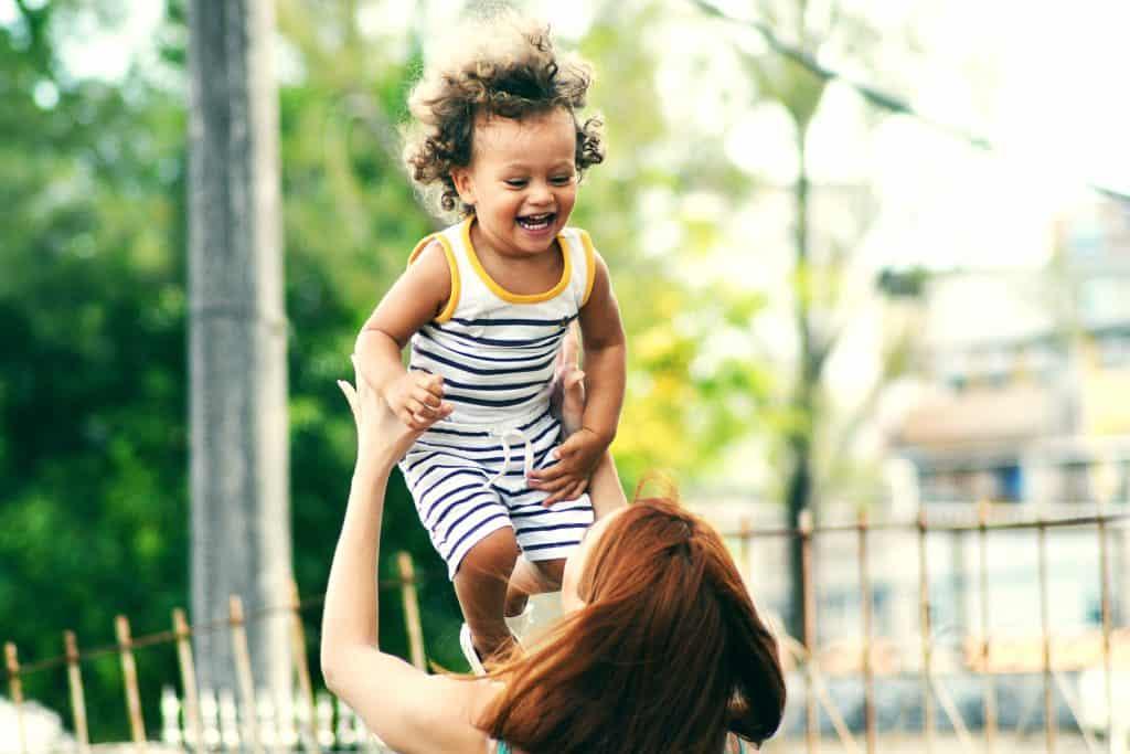 Na foto um menino sendo carregado por uma mulher sorrindo.